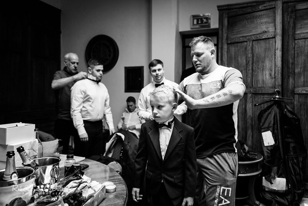 Pageboy has hair combed and groomsmen get ready for wedding at Stanbrook Abbey