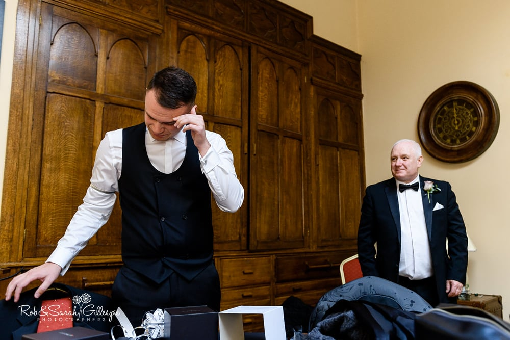 Groom gets emotional at gift from bride while getting ready for wedding at Stanbrook Abbey