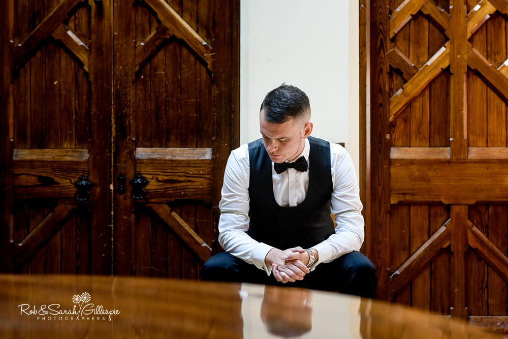 Groom takes a moment while getting ready for wedding at Stanbrook Abbey