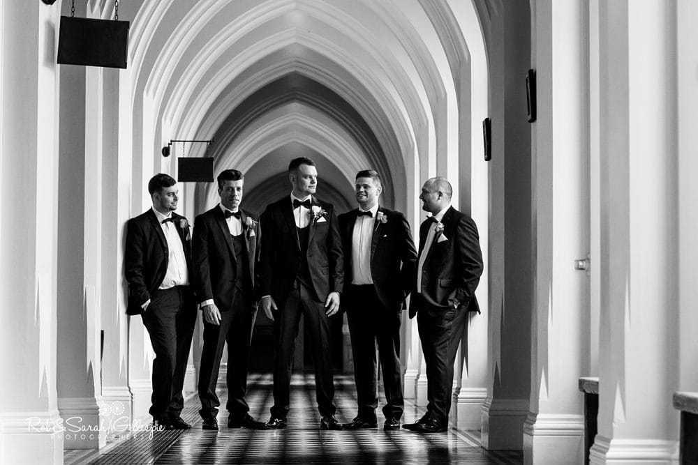 Groom and groomsmen pose for group photo in cloister corridor at Stanbrook Abbey