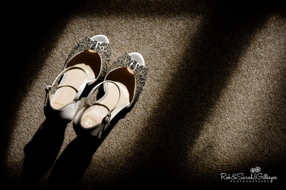 Bride's shoes in strong window light at Stanbrook Abbey