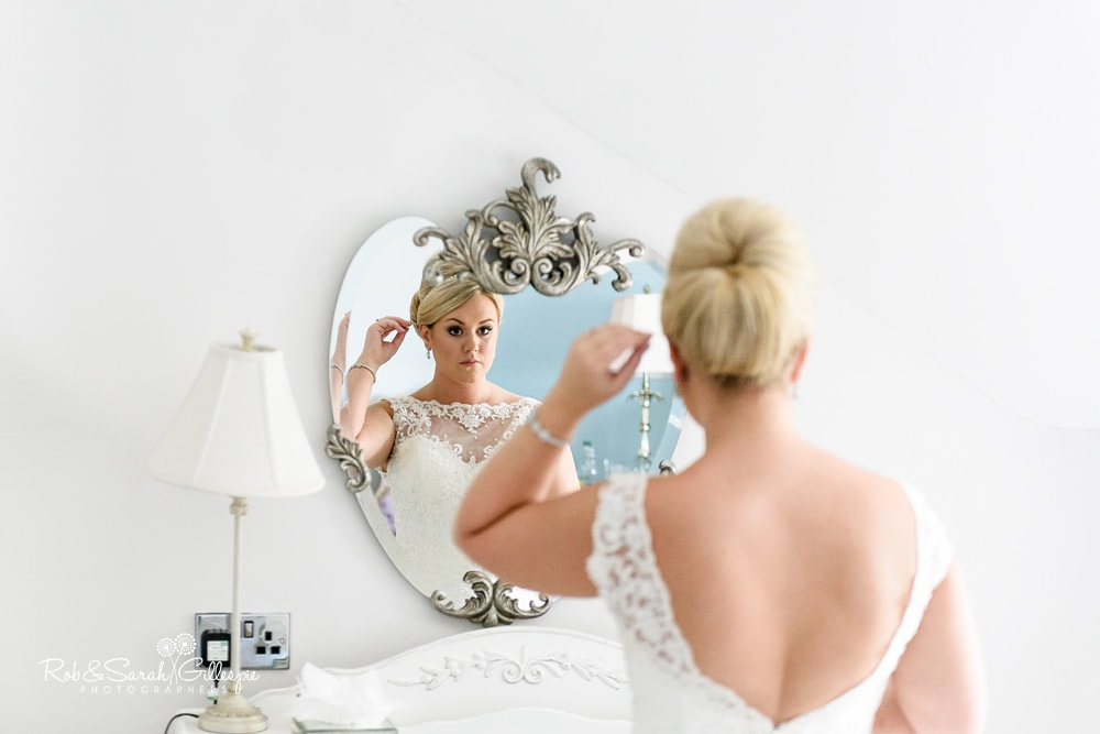 Bride looks in mirror and adjusts hair before wedding at Stanbrook Abbey Hotel