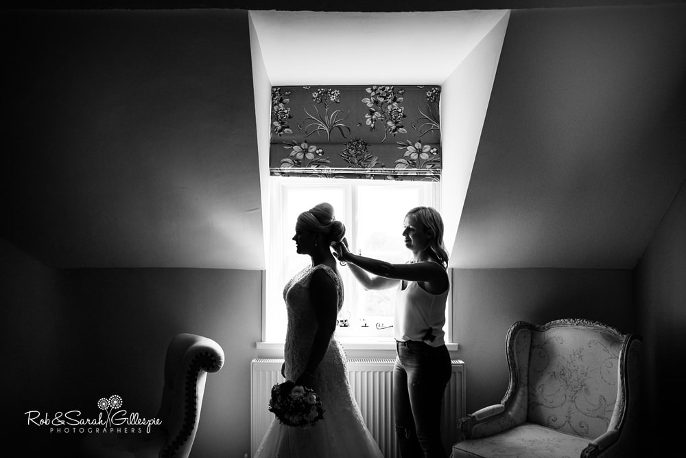 Bride in silhouette as she has hair adjusted at Stanbrook Abbey