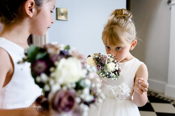 Flowergirl smells wedding flowers at Stanbrook Abbey