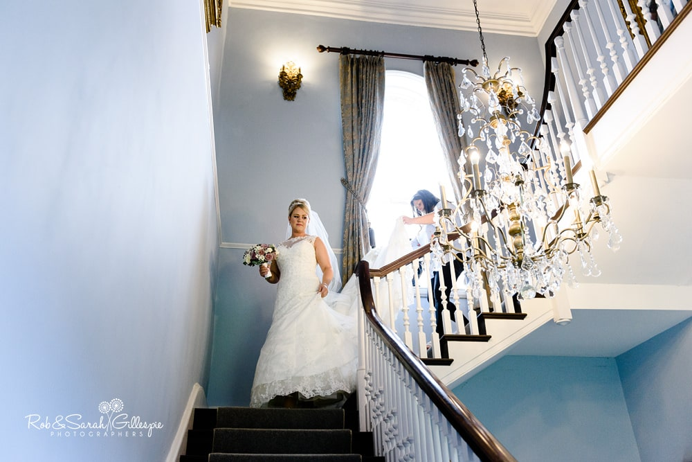 Bride walks down staircase at Stanbrook Abbey