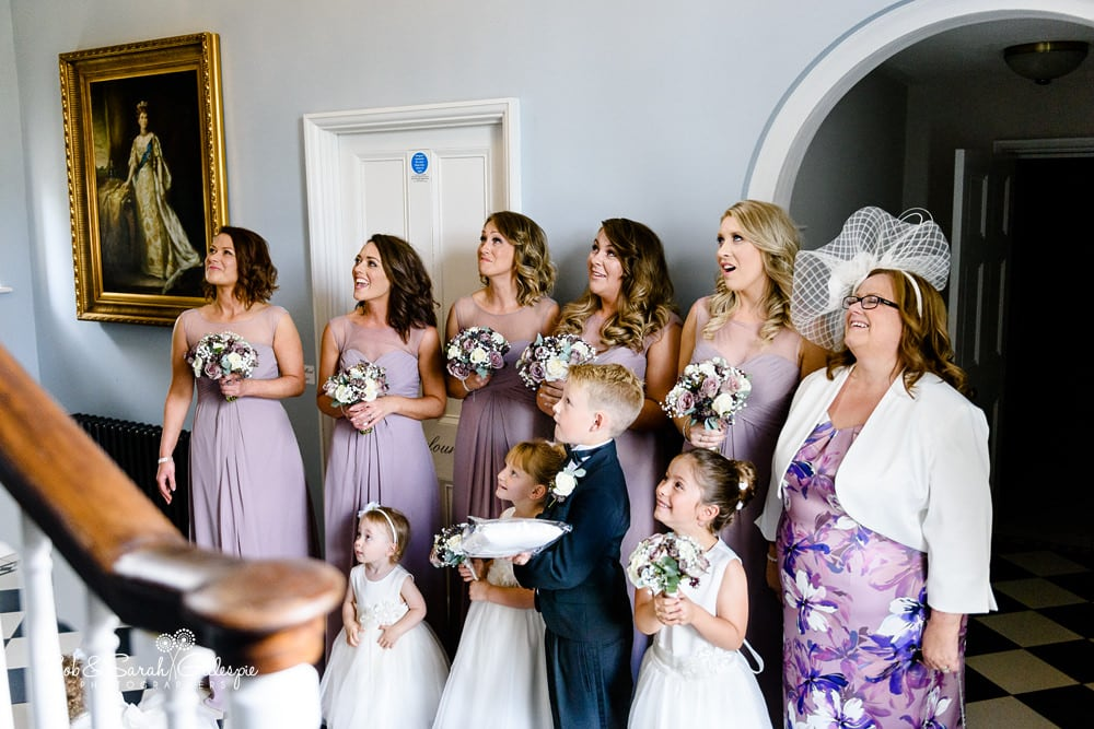 Bridesmaids and flower girls look at Bride as she walks down staircase at Stanbrook Abbey