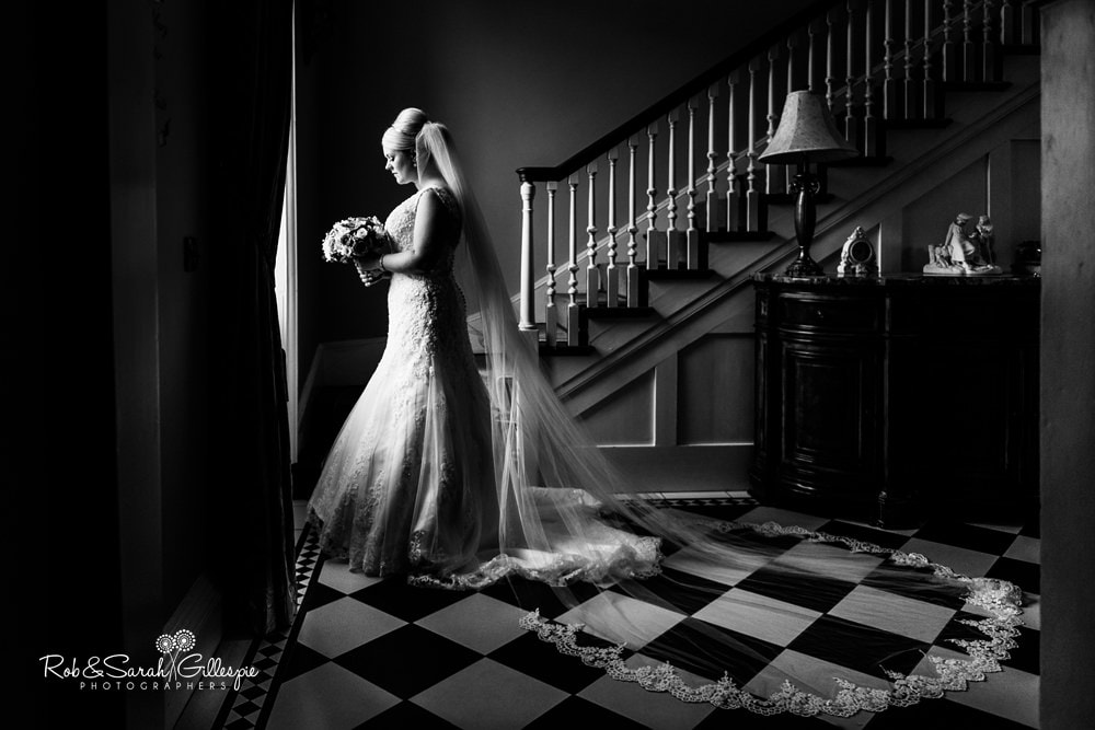 Dramatic black and white portrait of bride in beautiful light at Stanbrook Abbey with cathedral veil spread across tiled floor