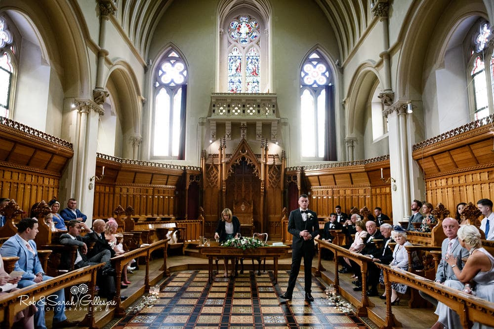 Groom and guests wait for ceremony in Callow Great Hall at Stanbrook Abbey