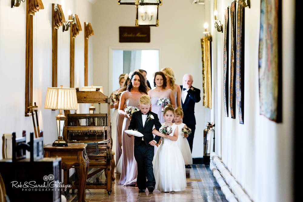 Pageboy flower girls and bridesmaids walk through corridor at Stanbrook Abbey