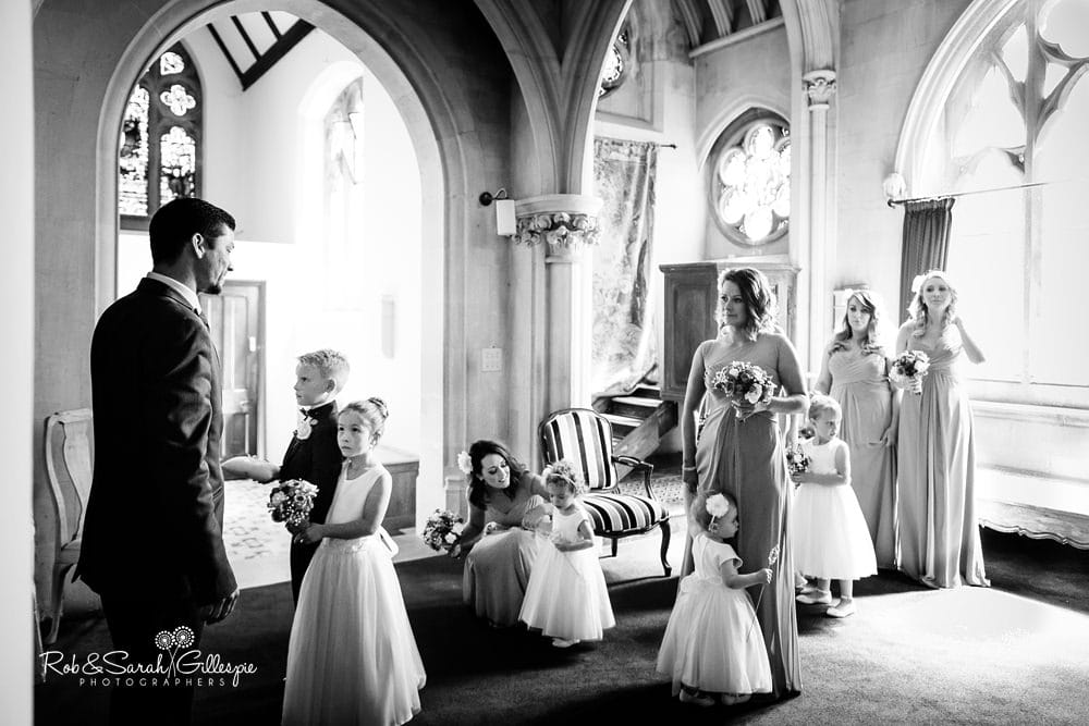 Black and white photograph at Stanbrook Abbey showing bridesmaids waiting for wedding ceremony to begin