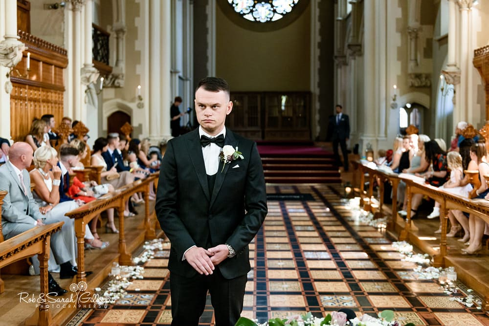 Groom looks nervous as he waits for wedding ceremony to begin at Stanbrook Abbey