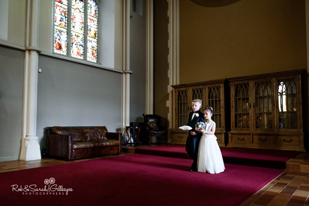 Page boy and flower girl enter Callow Hall at Stanbrook Abbey for wedding ceremony