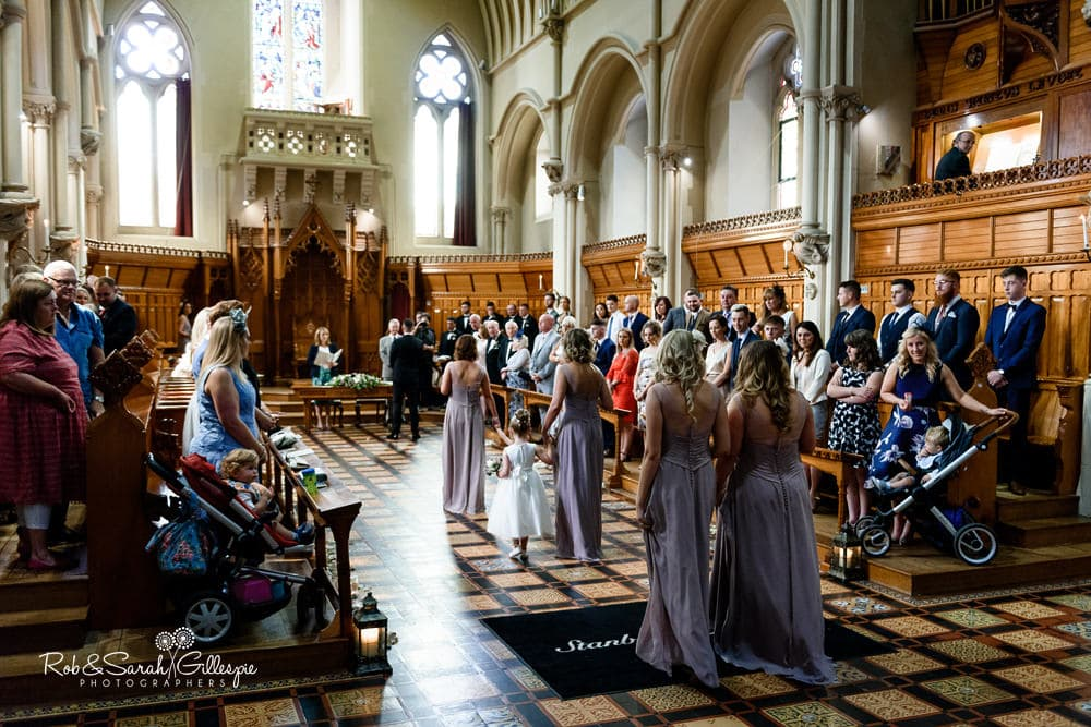 Groom waits for bride as page boy and bridesmaids enter Callow Hall at Stanbrook Abbey