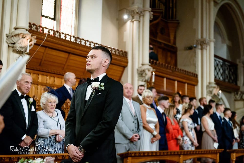 Groom waits for bride in Callow Great Hall at Stanbrook Abbey wedding ceremony