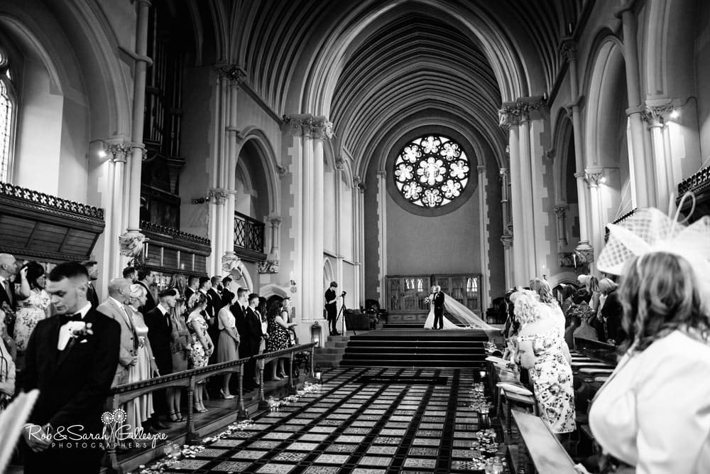 Bride and father make entrance in Callow Hall at Stanbrook Abbey as groom waits