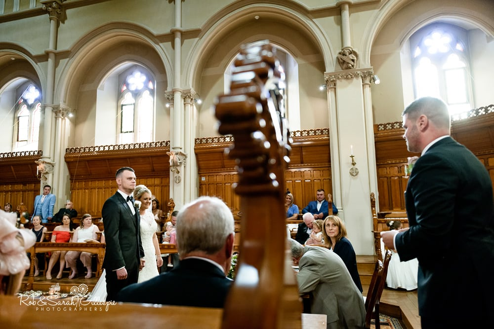 Guest gives reading during wedding ceremony at Stanbrook Abbey as bride and groom listen and smile