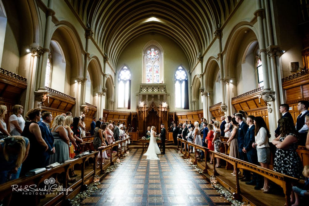 Wide angle view of bride and groom during wedding ceremony at Stanbrook Abbey with guests