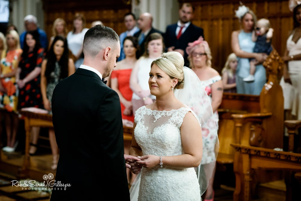 Bride and groom exchange wedding rings during Stanbrook Abbey ceremony