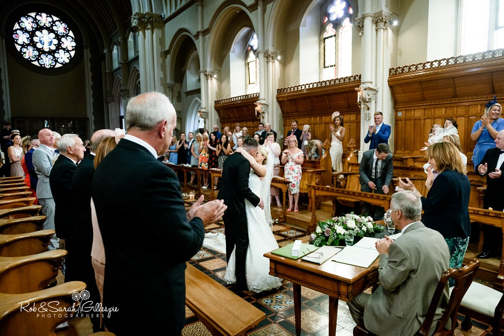 Bride and groom kiss in Callow Great Hall at Stanbrook Abbey
