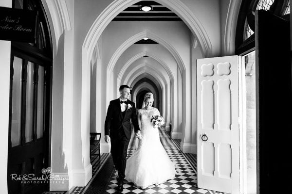 Bride and groom walk through arched corridor at Stanbrook Abbey