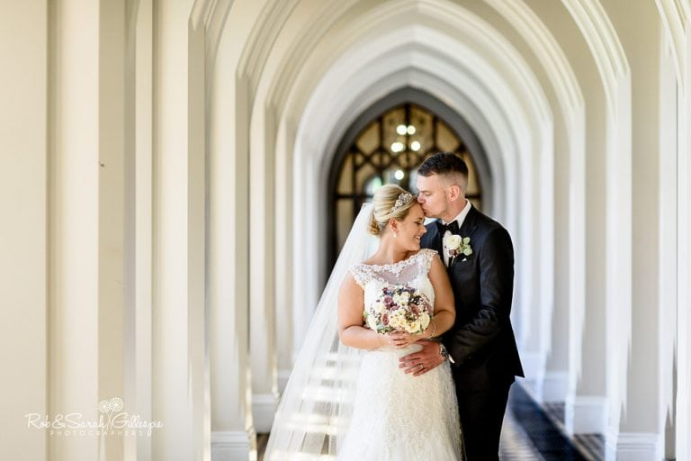 Bride and groom in arched cloisters at Stanbrook Abbey