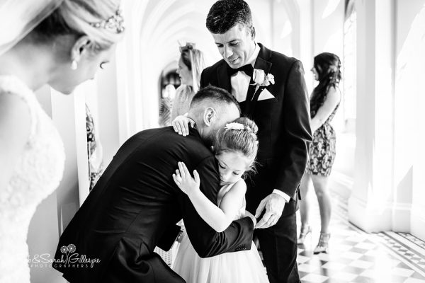 Flowergirl hugs groom at Stanbrook Abbey wedding