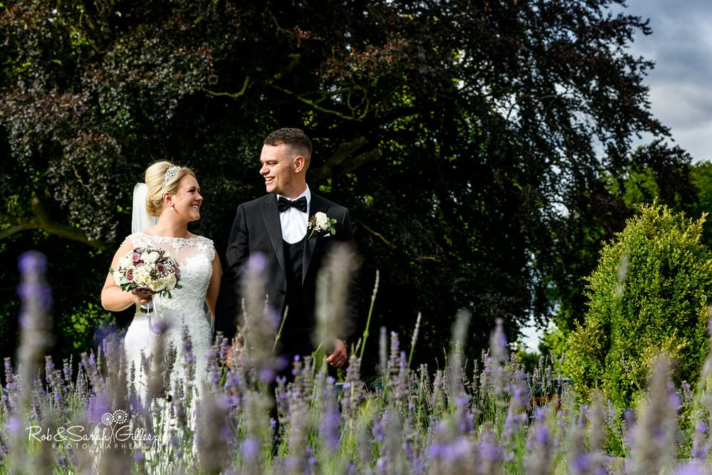 Bride and groom walk through heather at Stanbrook Abbey wedding