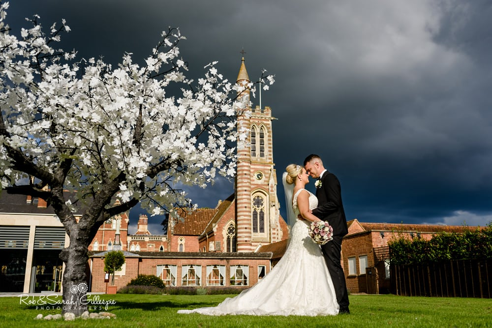 Bride and groom together at Stanbrook Abbey with beautiful architecture and dramatic sky