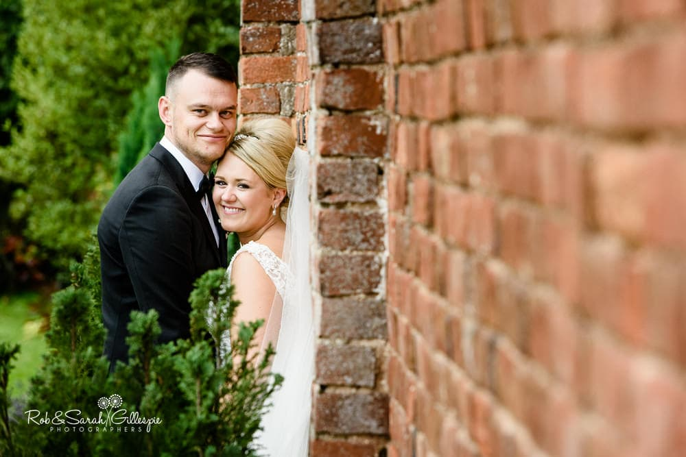 Bride and groom share a laugh during photo shoot at Stanbrook Abbey