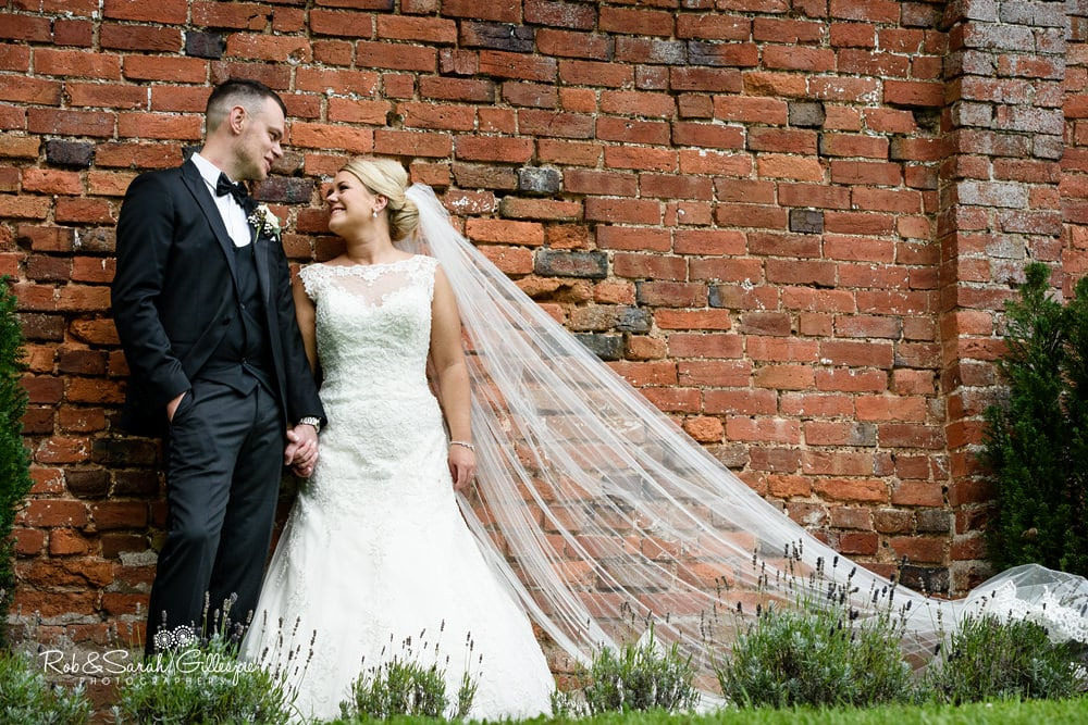 Bride and groom together in grounds of Stanbrook Abbey on their wedding day