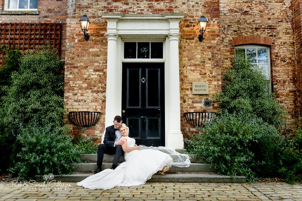 Bride and groom sitting on steps of Brides Manor at Stanbrook Abbey