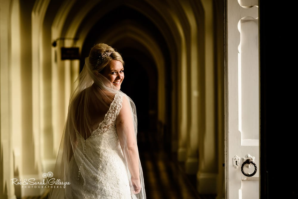 Bride stands in corridor at Stanbrook Abbey