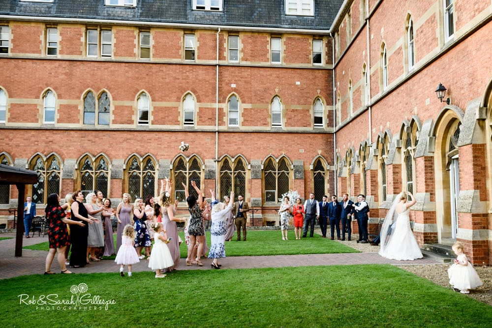 Bride throws bouquet at Stanbrook Abbey wedding