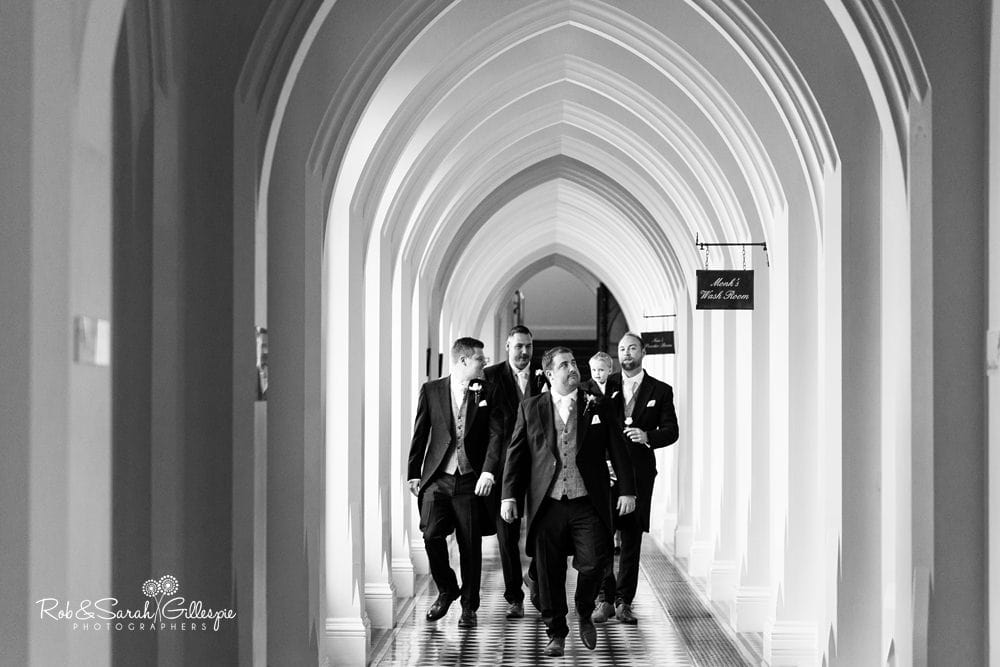 Groom and ushers walking through cloisters at Stanbrook Abbey