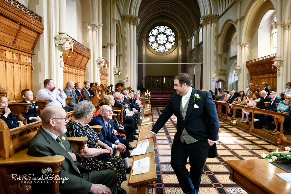 Groom chats with wedding guests in Callow Great Hall before wedding ceremony