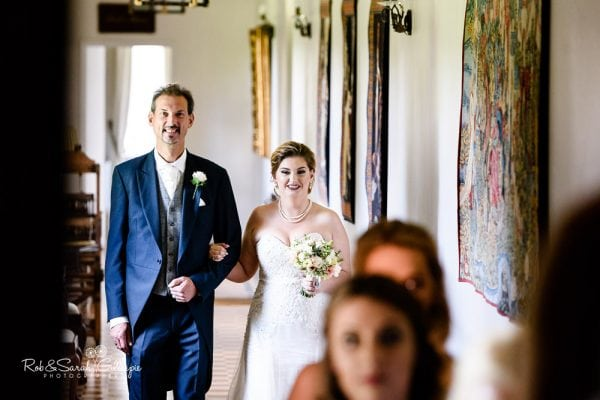 Bride and father walk to wedding ceremony at Stanbrook Abbey