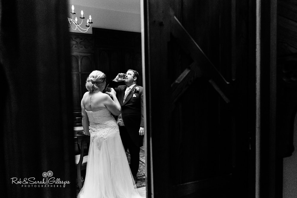 Bride and groom share a drink at end of wedding ceremony at Stanbrook Abbey