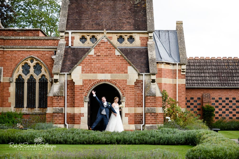 Bride and groom walk through gardens at Stanbrook Abbey