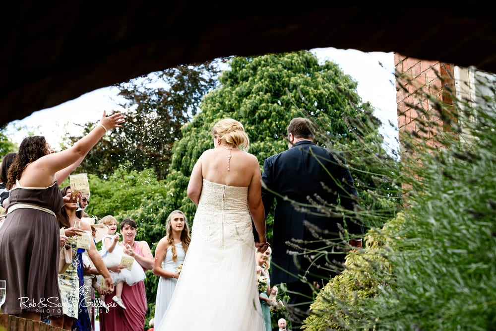 Wedding guests throw confetti at Stanbrook Abbey wedding