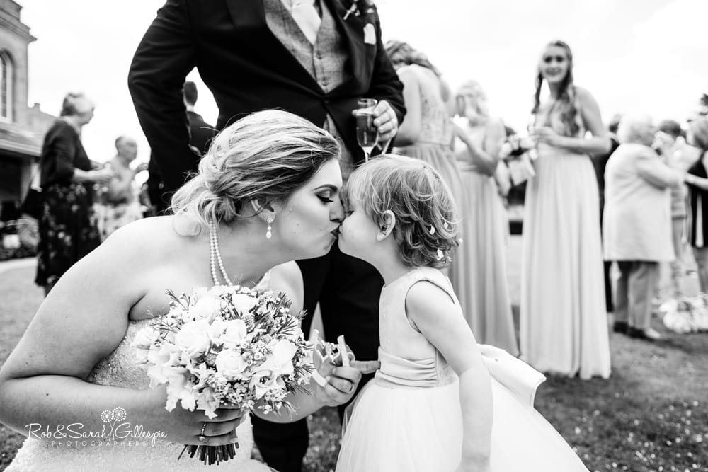 Bride and groom hug and chat with guests during drinks reception at Stanbrook Abbey wedding