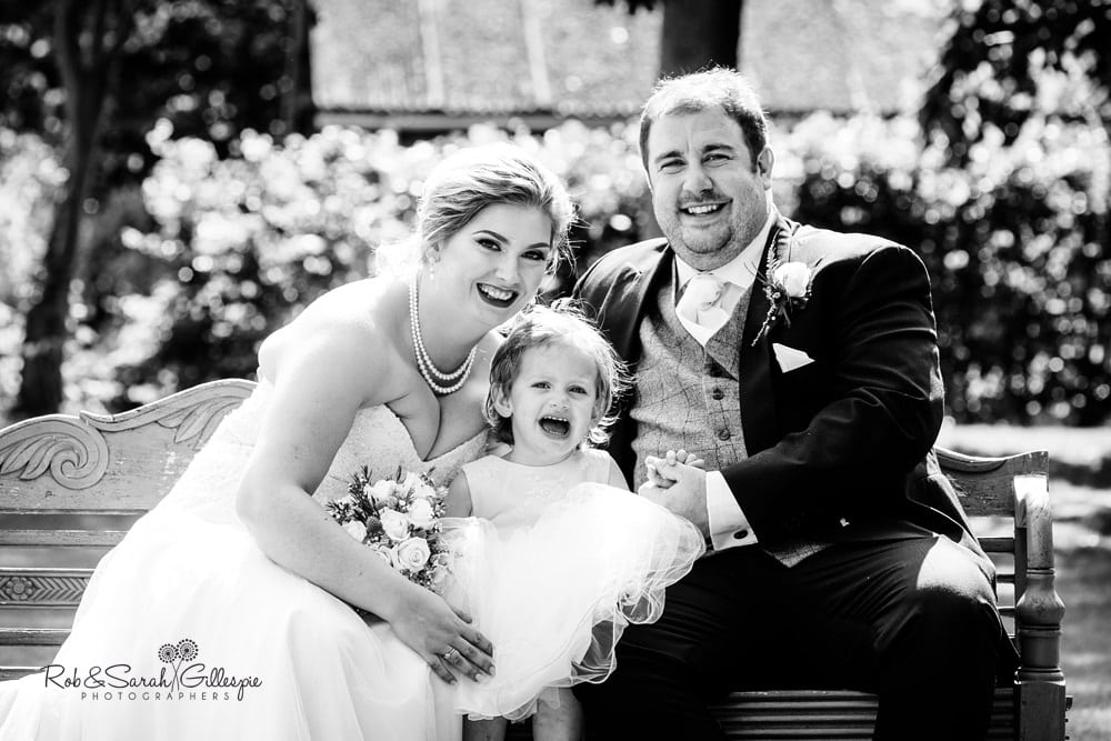 Bride, groom and young daughter during drinks reception at Stanbrook Abbey wedding