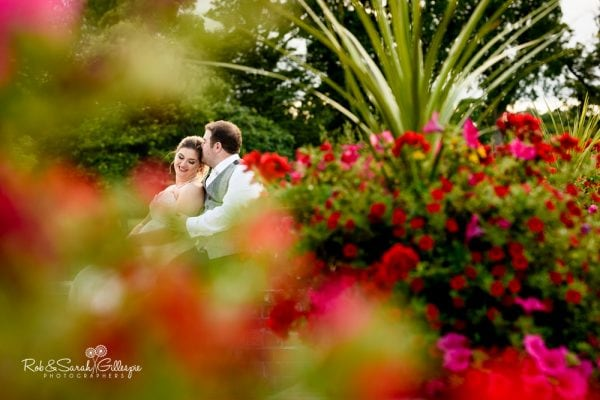 Bride and groom surrounded by flowers at Stanbrook Abbey