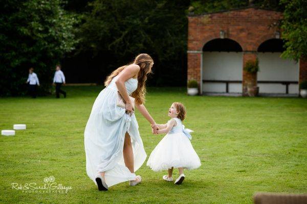 Bridesmaid and flowergirl run across lawn at Stanbrook Abbey