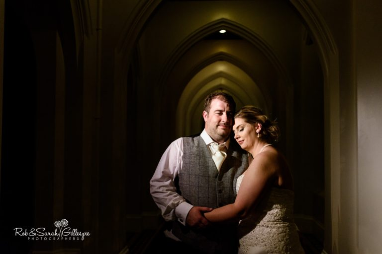 Bride and groom cuddled up in arched corridor at Stanbrook Abbey