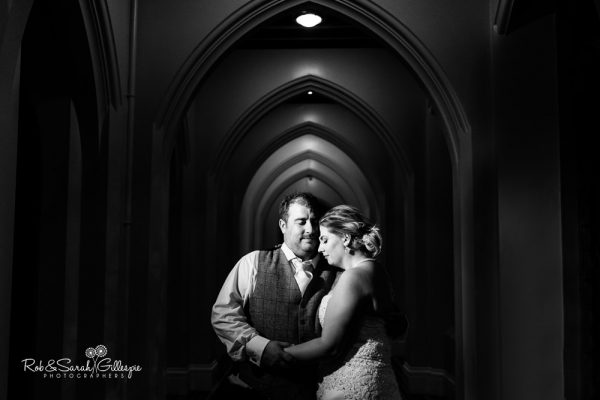 Bride and groom in arched corridor at Stanbrook Abbey