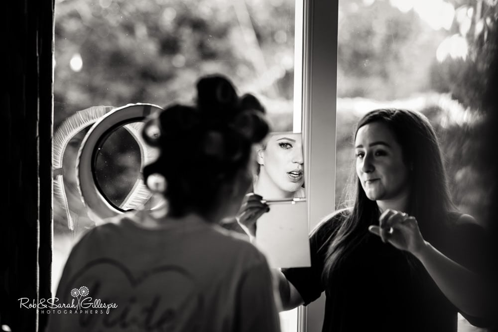 Bride checks make-up in mirror, held by MUA Chloe McCall
