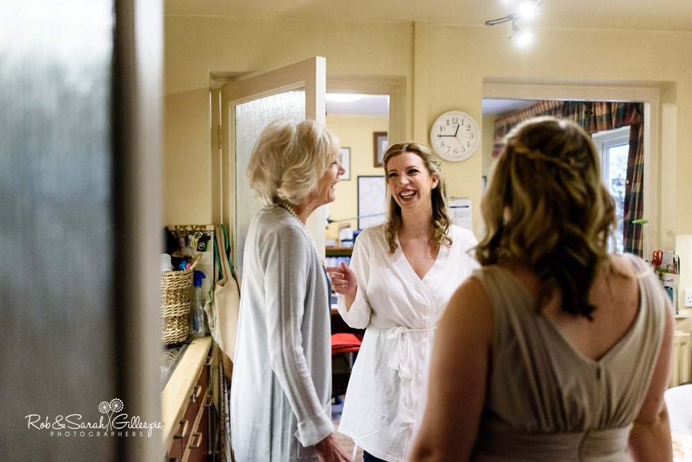 Bride laughing with bridesmaid and relation while getting ready fro wedding