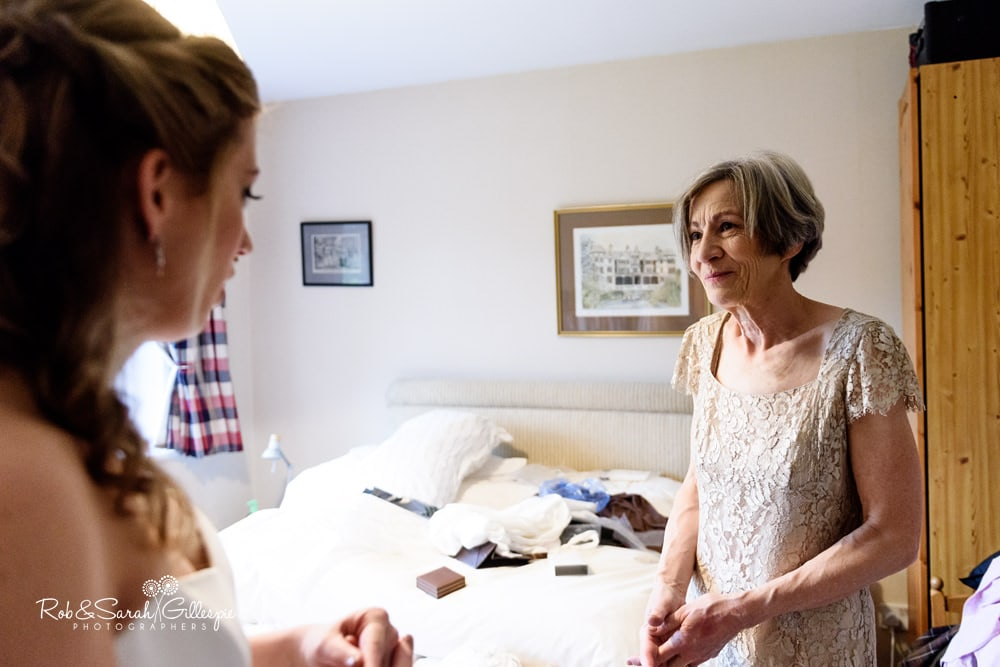 Bride's mum smiling at daughter as she gets ready for her wedding