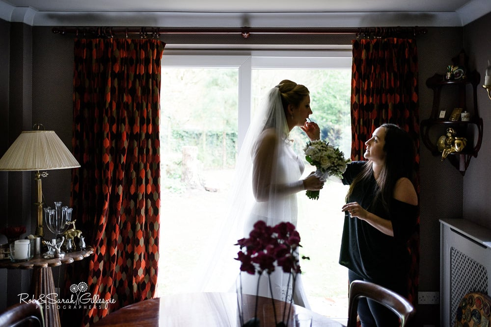 Bride has final make-up applied before wedding, silhouetted in window light