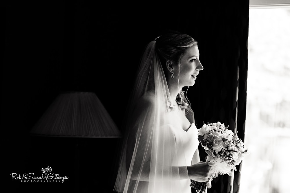 Black and white portrait of bride wearing long veil, looking out of window